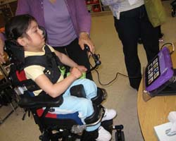 "Young girl using a ""Super Talker"" with adaptive equipment to communicate."